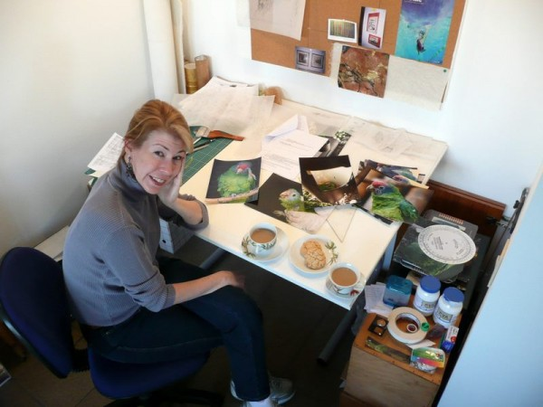 Kitty Harvill at her desk with her feathered muses